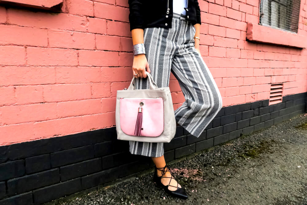 Unknown fashionable woman with striped slacks and statement bag