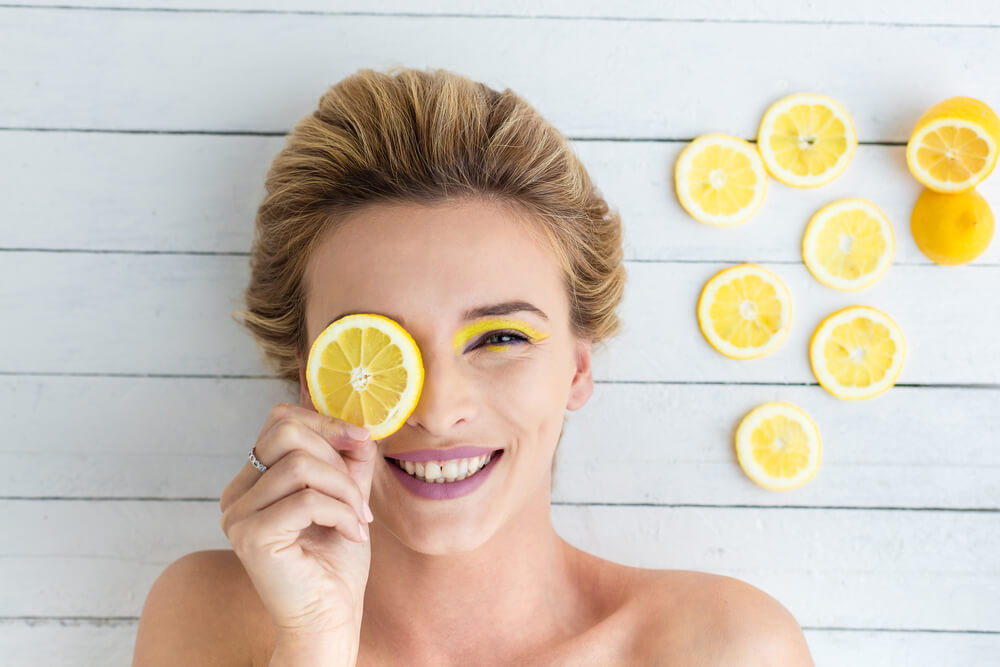 Smiling young woman with a slice of lemon
