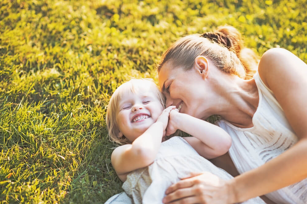 Happy mother playing with her child on the grass