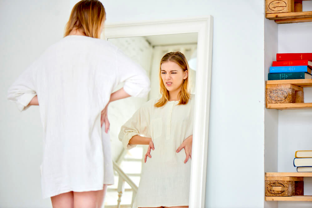 Woman checking body size in the mirror