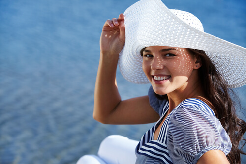 Woman covering herself with a sun hat