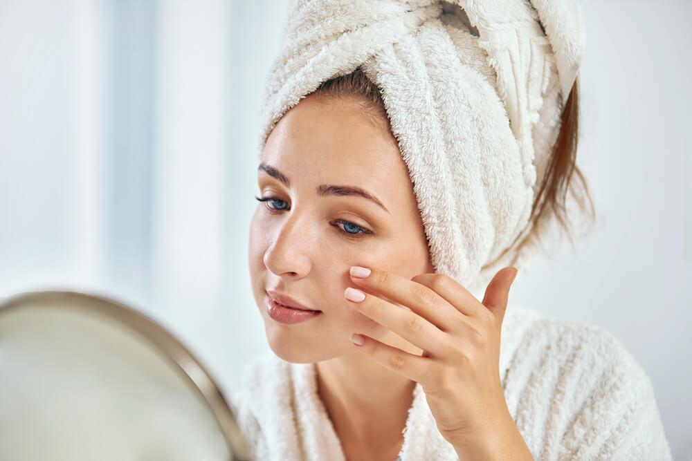 woman cleaing up skin in front of a mirror