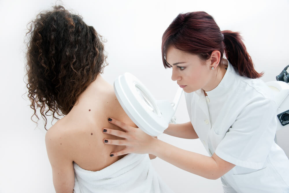 Doctor examining patient's back for skin spots