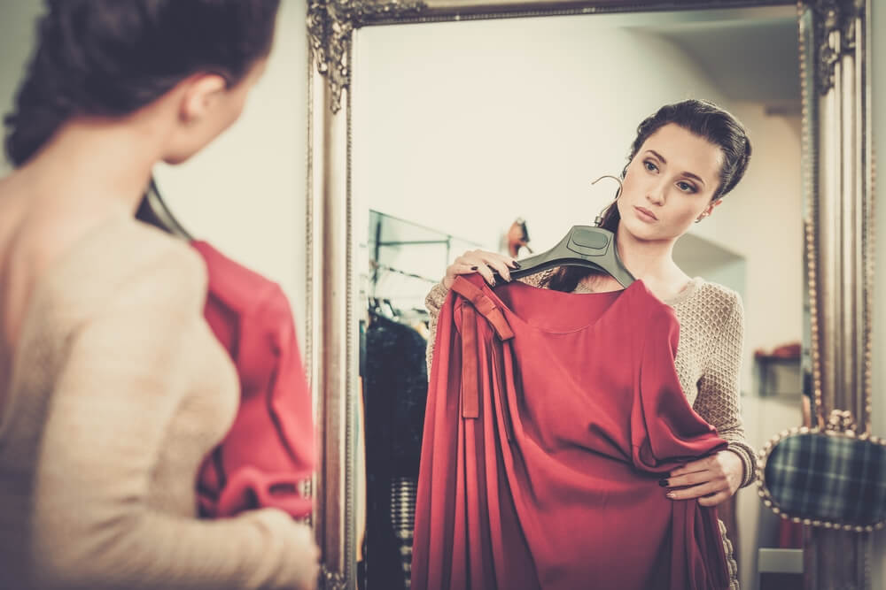 Woman trying on red dress in front of mirror