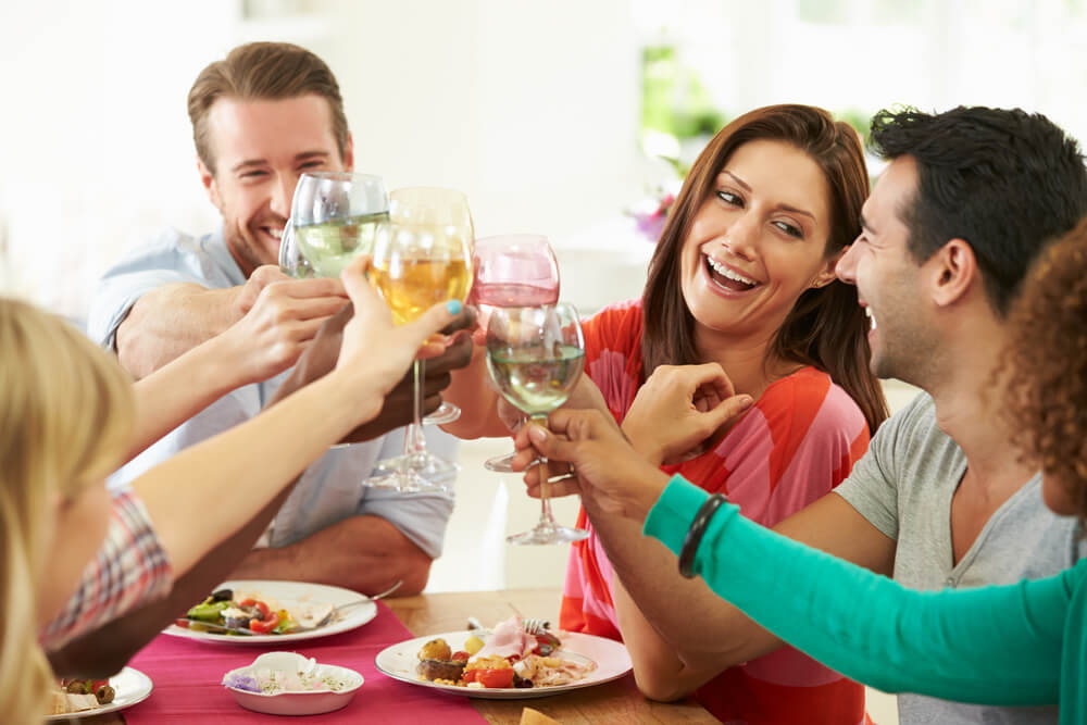 Friends clinking wine glasses over lunch table