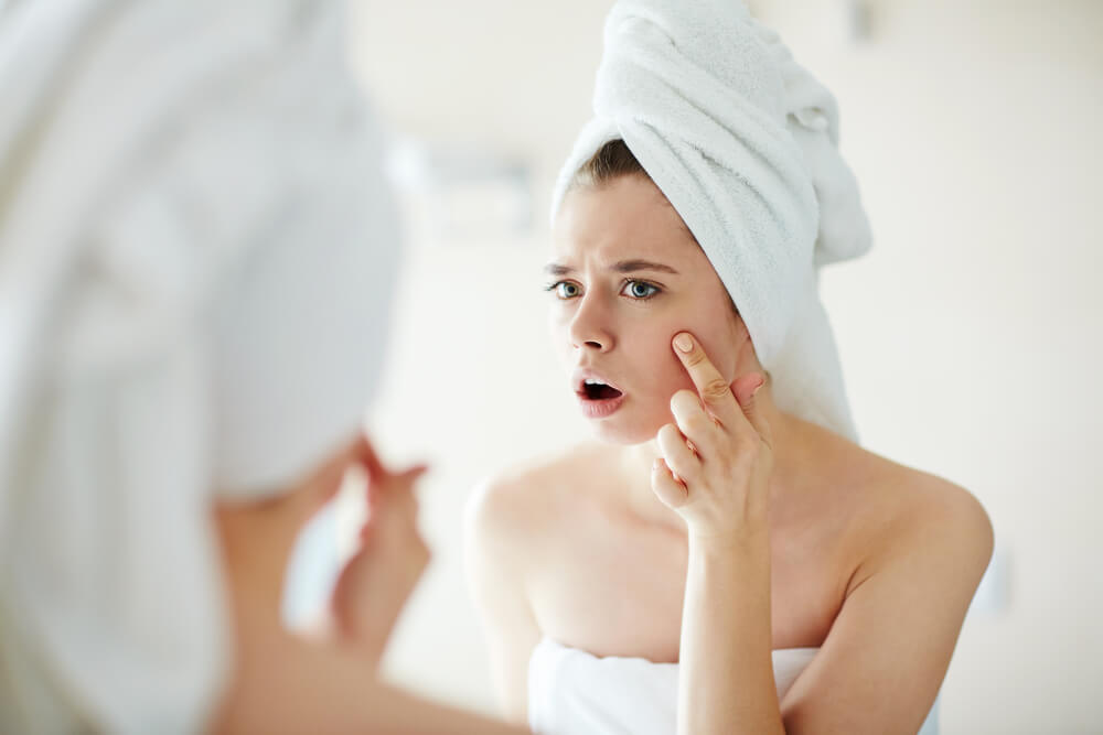 Woman frowning upon discovering a pimple on her face
