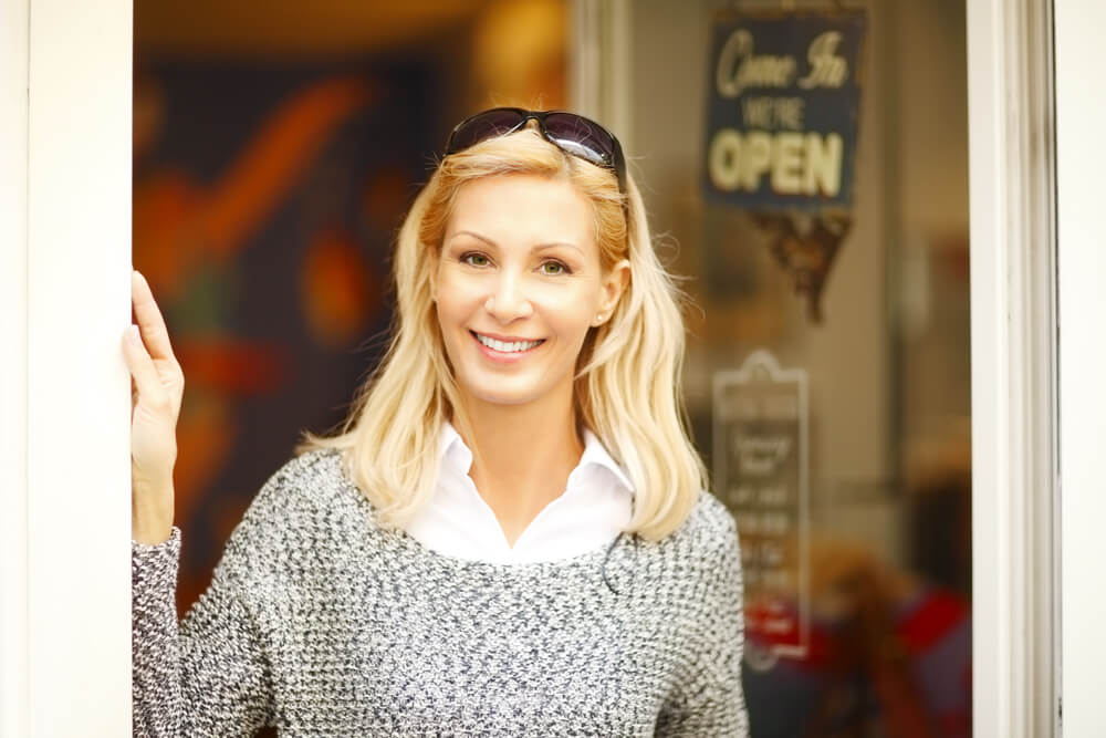 Smiling middle-age blonde woman outside a cafe