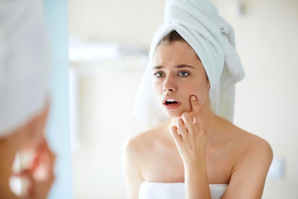 Unhappy woman pointing at pimple in the mirror