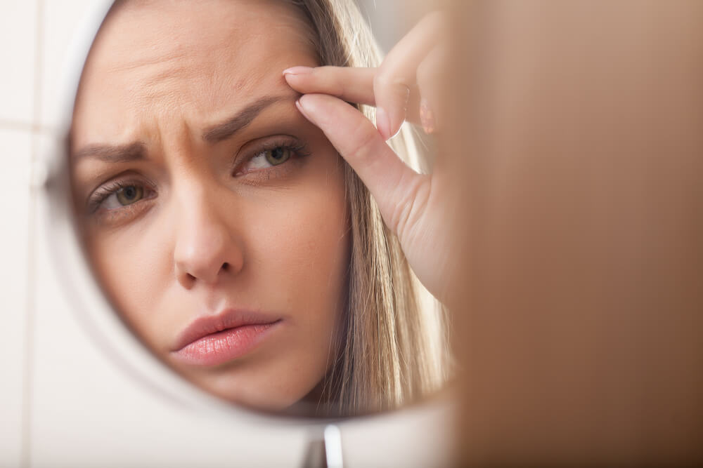 Woman frowning while examining forehead wrinkles in a dressing mirror
