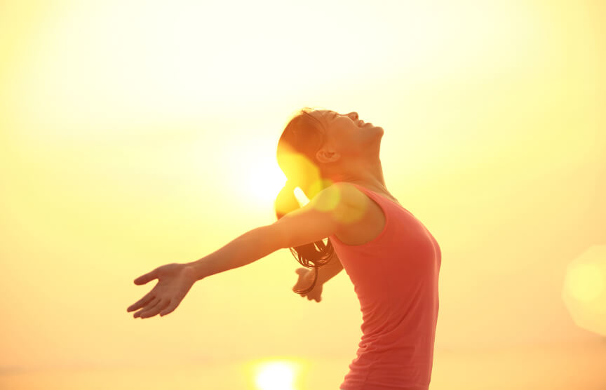 Happy woman with arms outstretched against the sun