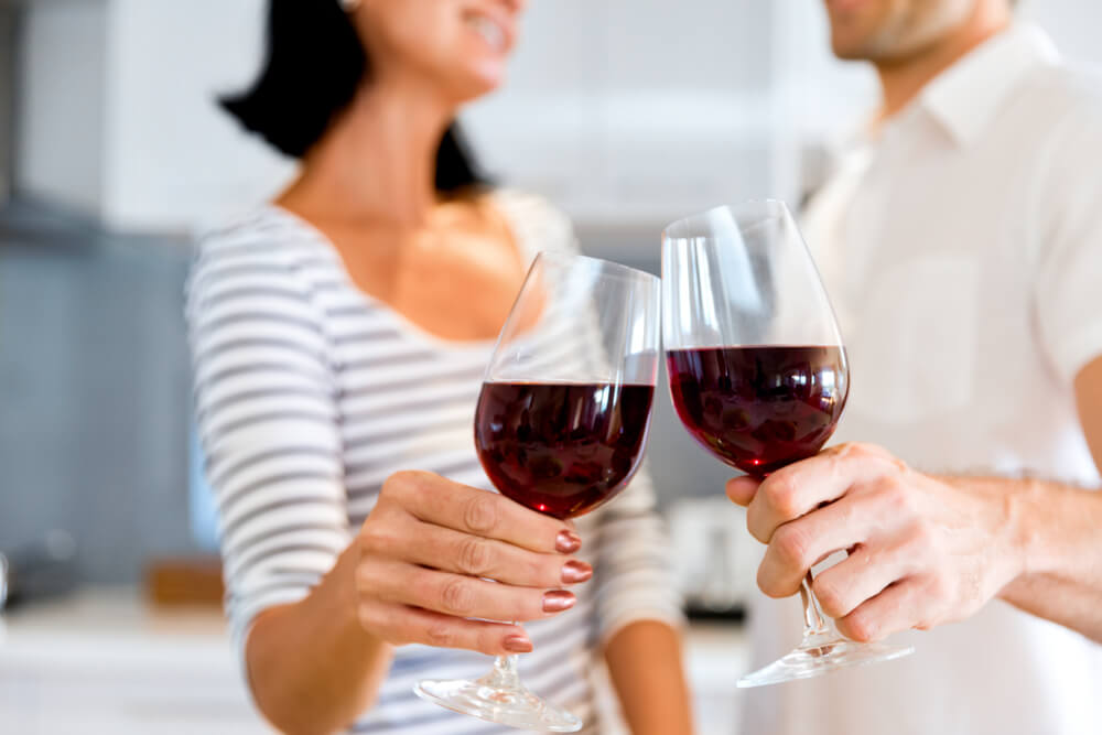 Unknown couple clinking wine glasses together