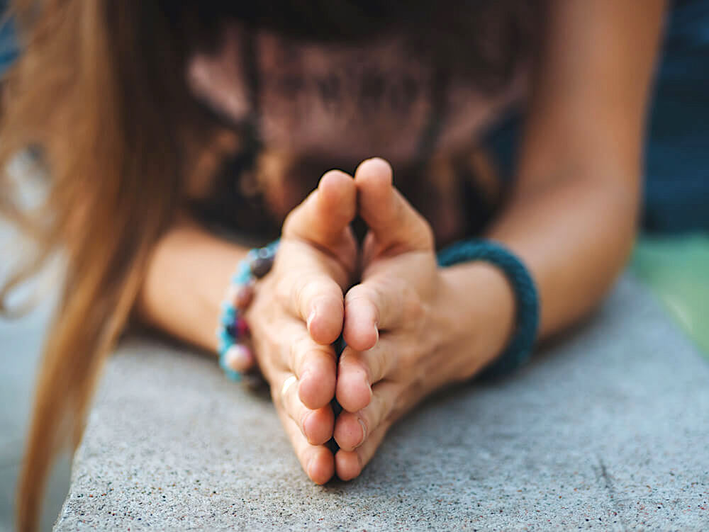 Unknown woman's hands pressed together in gratitude