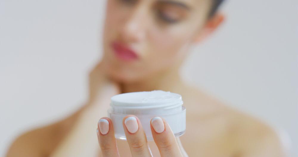 woman holding skin cream