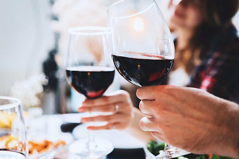 Clinking two wine glasses together over dinner table