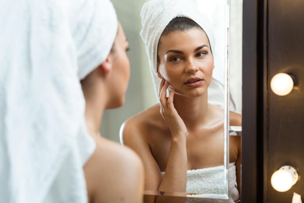 Young woman touching skin in front of bathroom mirror