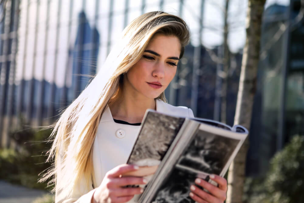 Young woman reading a magazine outdoors