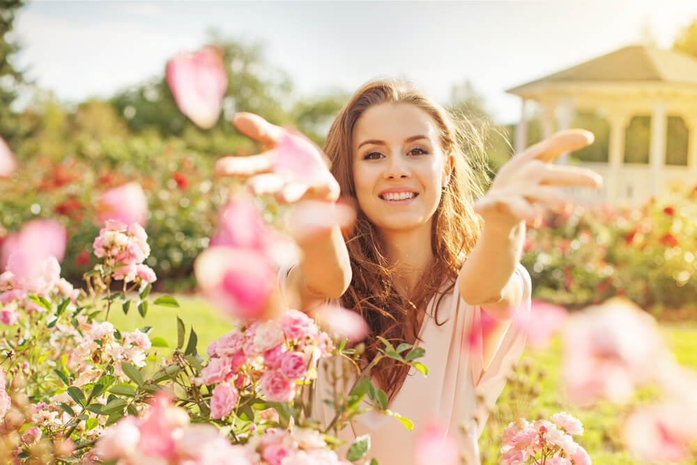 Young woman sprinkling flower petals during spring