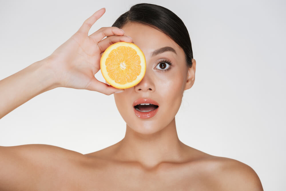 Woman with clear skin holding a slice of orange to her eye