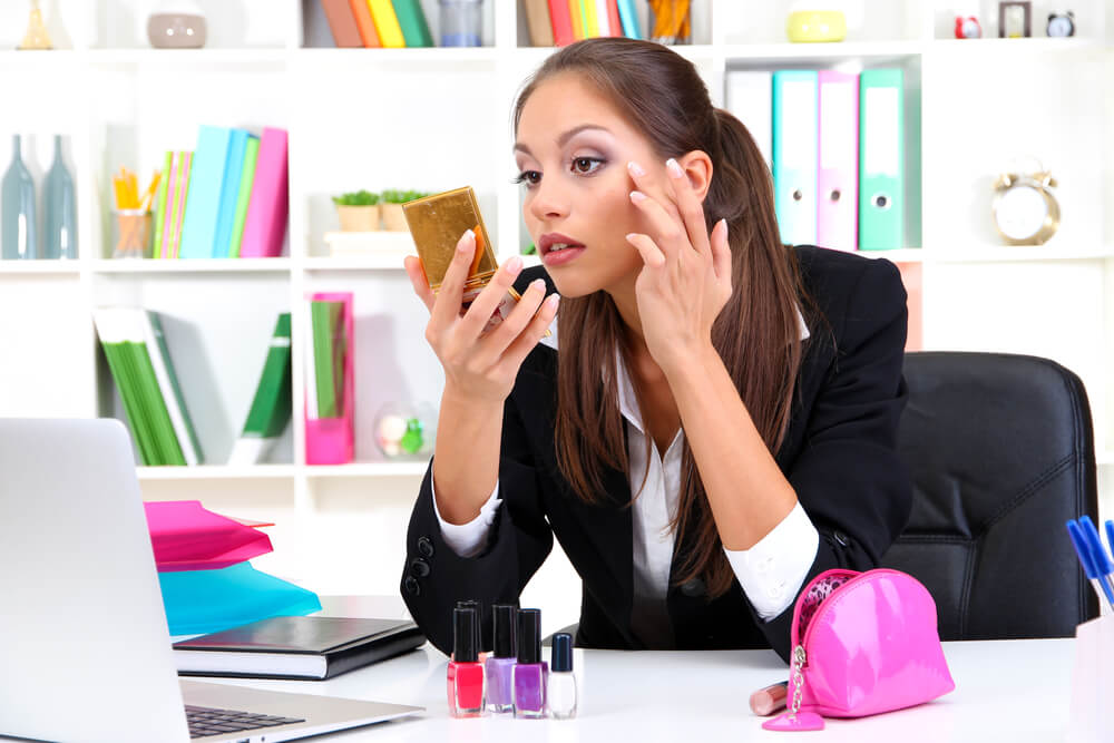 Young woman checking her skin in a compact mirror at her work desk