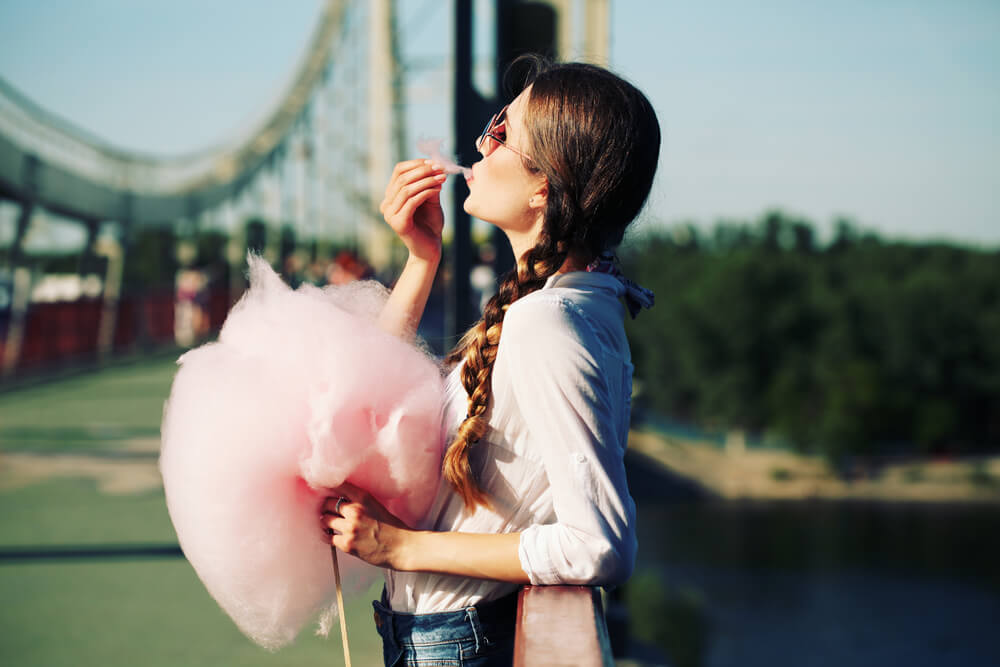 Young woman eating cotton candy outdoors