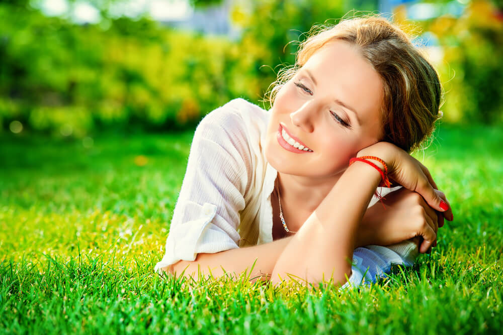 Happy and smiling woman lying on grass