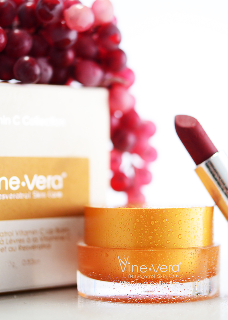 Resveratrol Vitamin C Lip Balm with a grape background