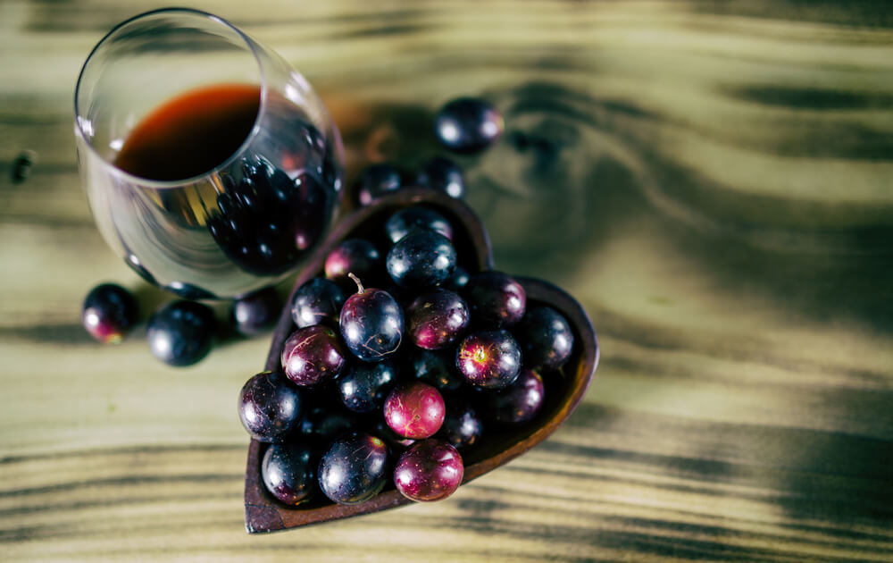 Glass of wine with a heart-shaped bowl of red grapes