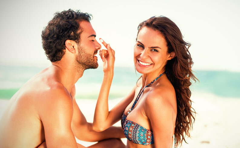 Couple applying sunscreen on the beach