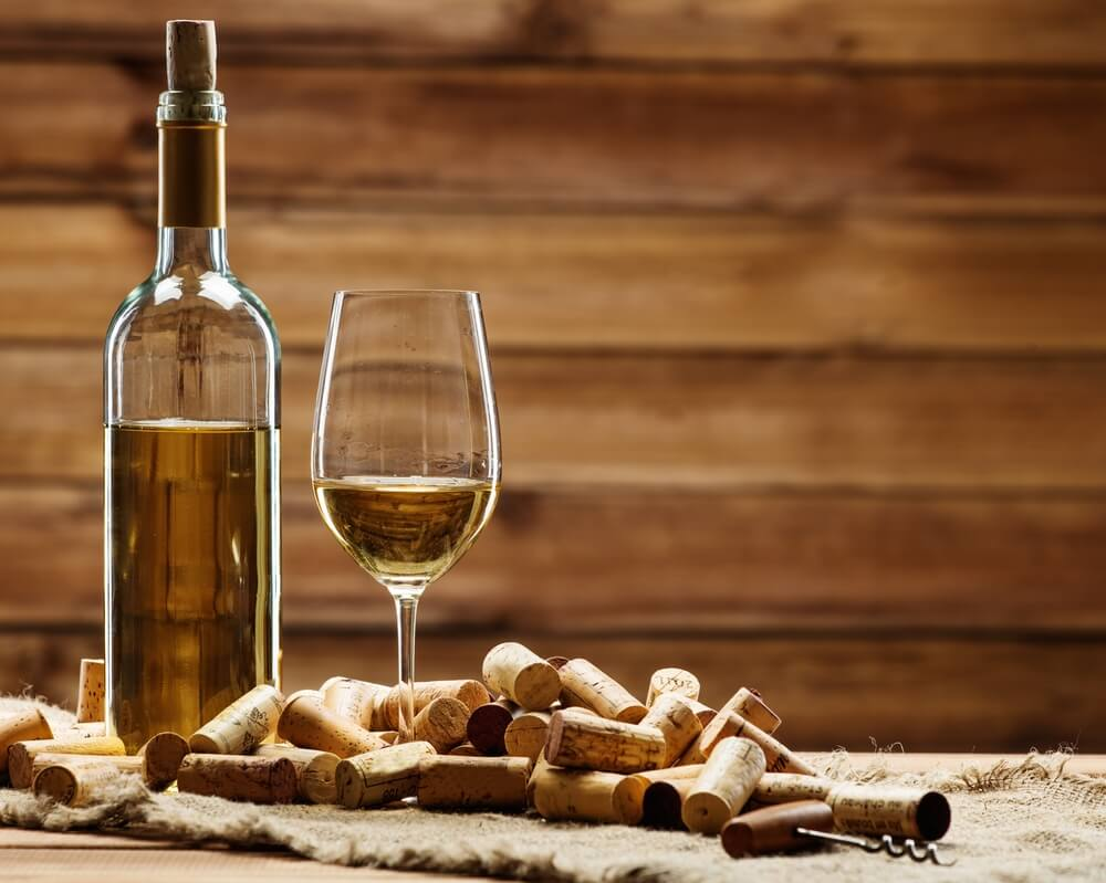 A bottle and glass of white wine on rustic setting