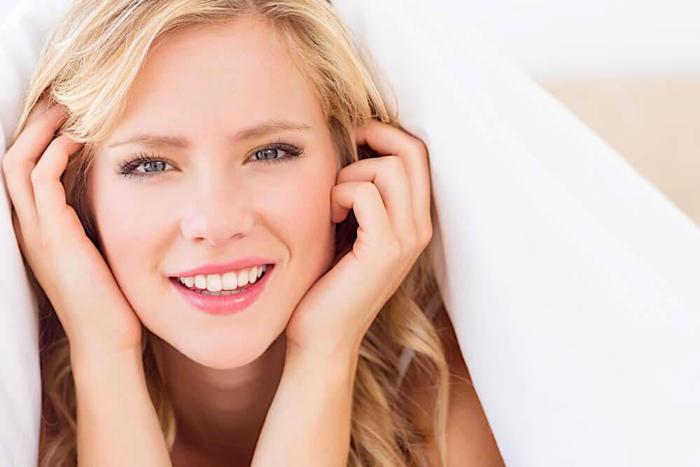 Pretty young woman smiling and touching her face