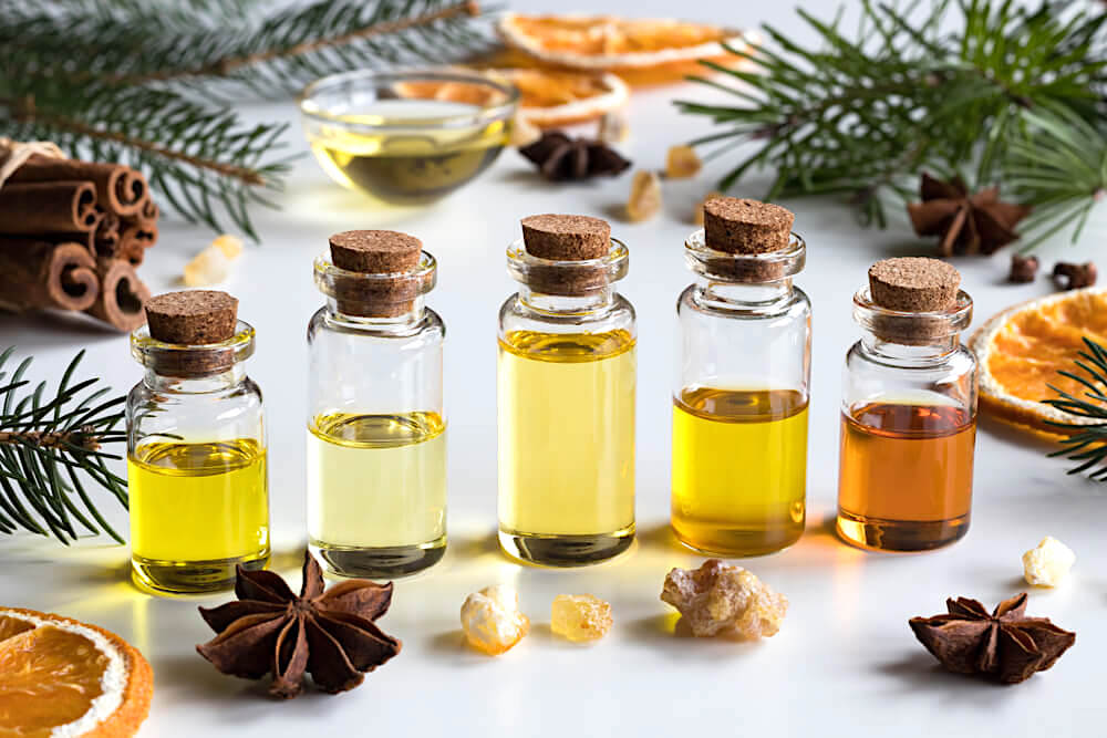 Small vials of essential oils surrounded by herbs