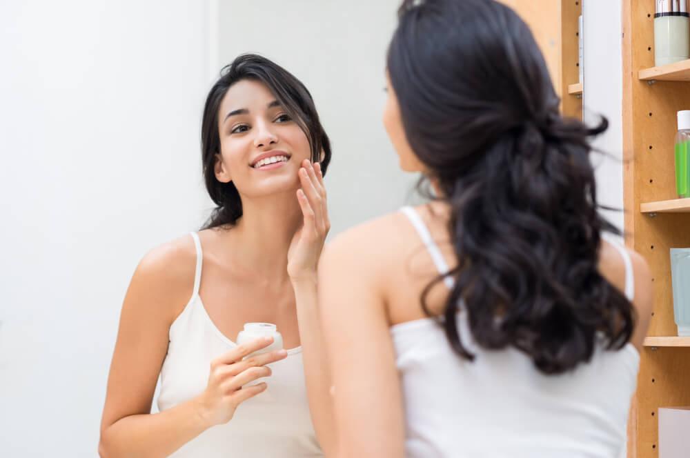 Woman applying moisturiser to skin