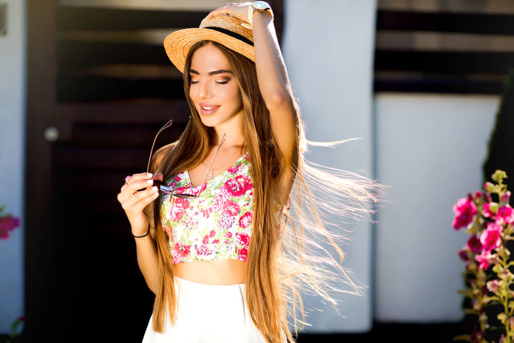 Young woman with long hair and hat outdoors during summer