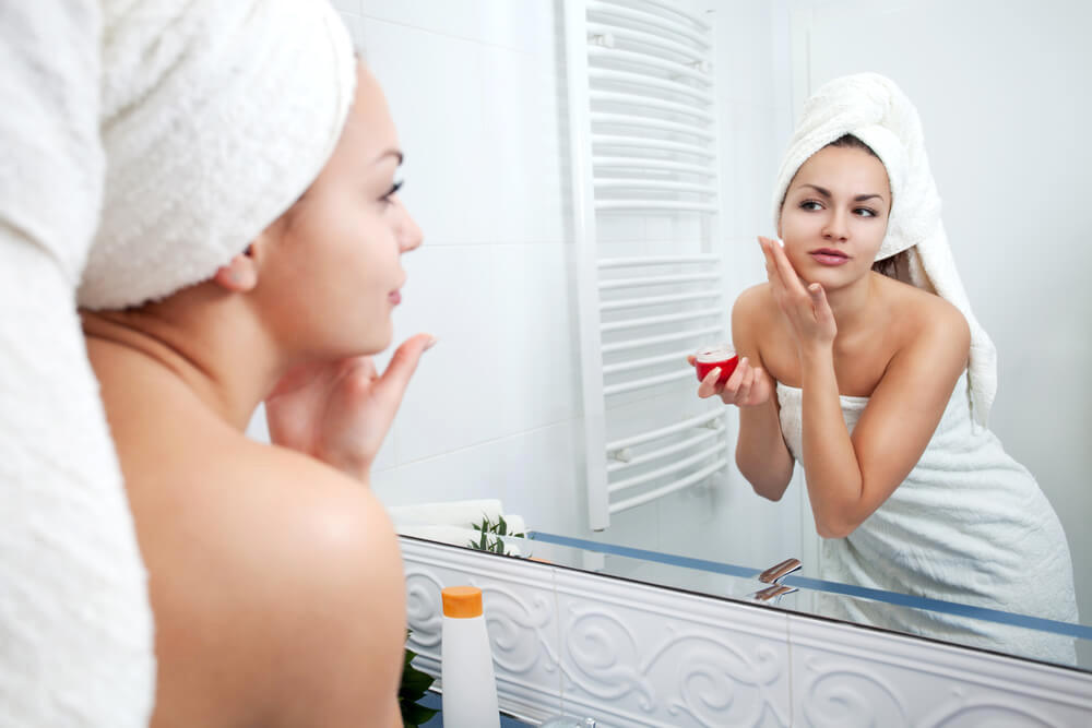 Young woman applying skincare in front of bathroom mirror