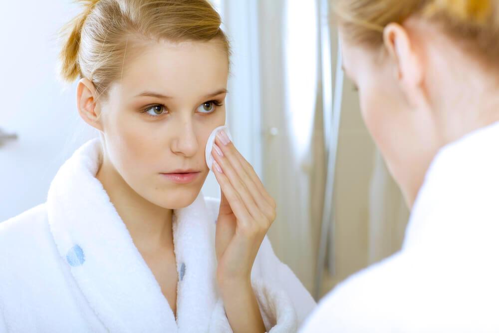 Woman applying skincare using a cotton pad