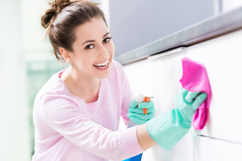 Young woman spring cleaning in the kitchen
