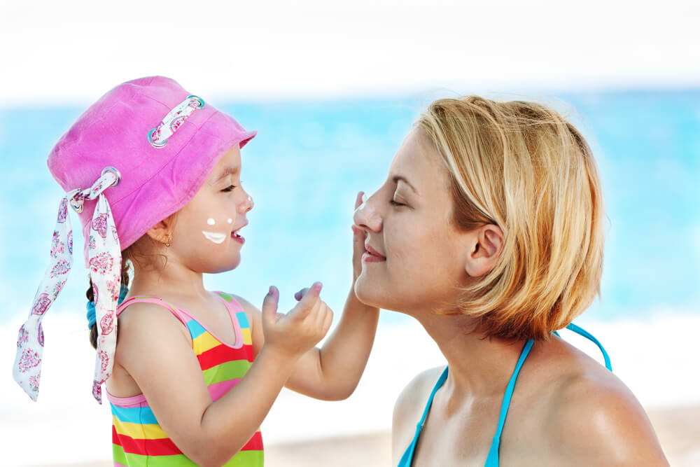 Little girl applying sunscreen on her mom's face