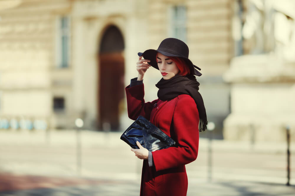 Fashionable woman in coat, scarf and hat outdoors