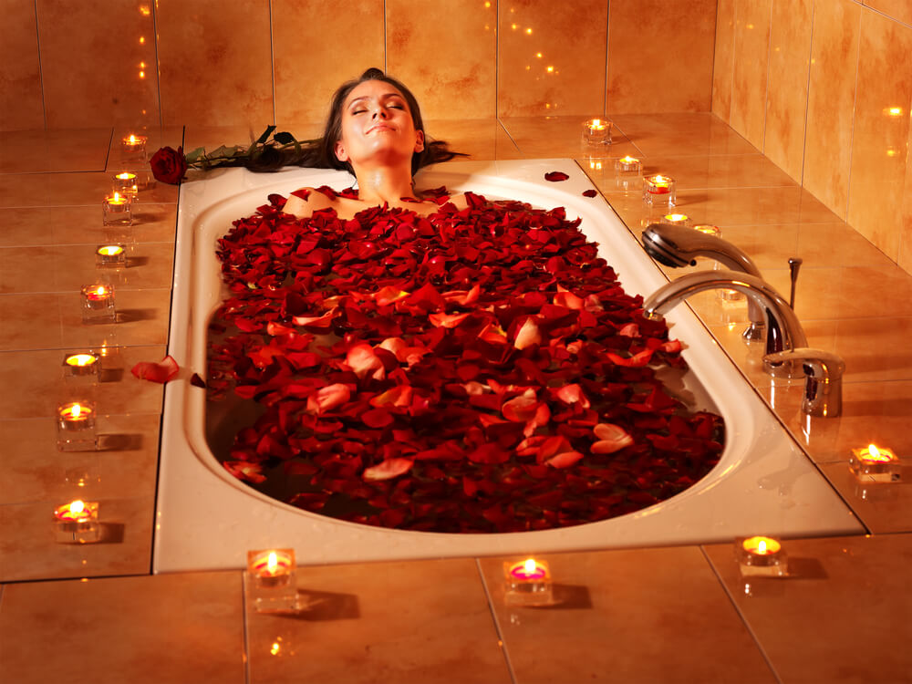 Young woman enjoying a bath filled with rose petals