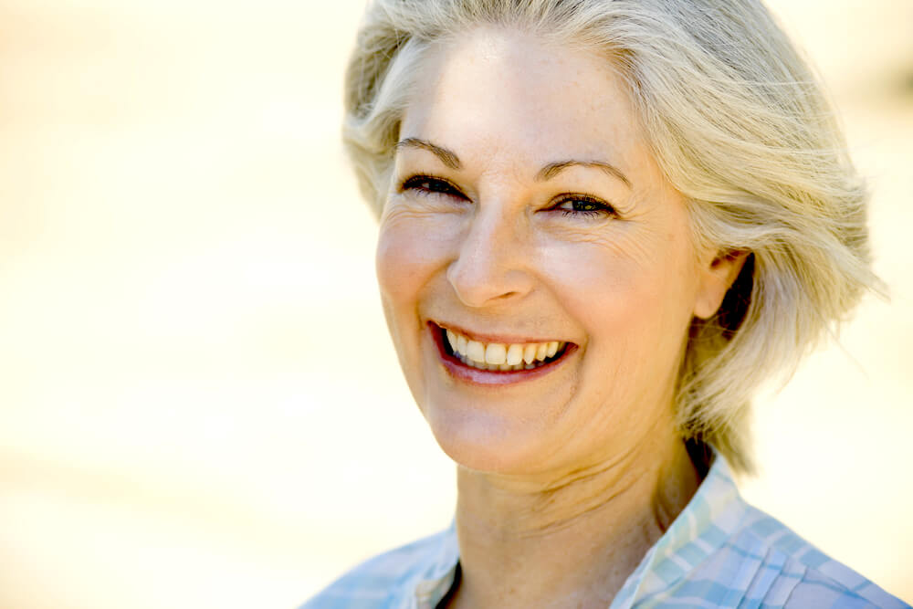 Happy smiling woman in her 50s or 60s with white hair