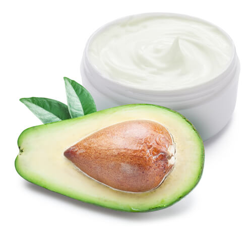 Halved avocado with a jar of moisturizer