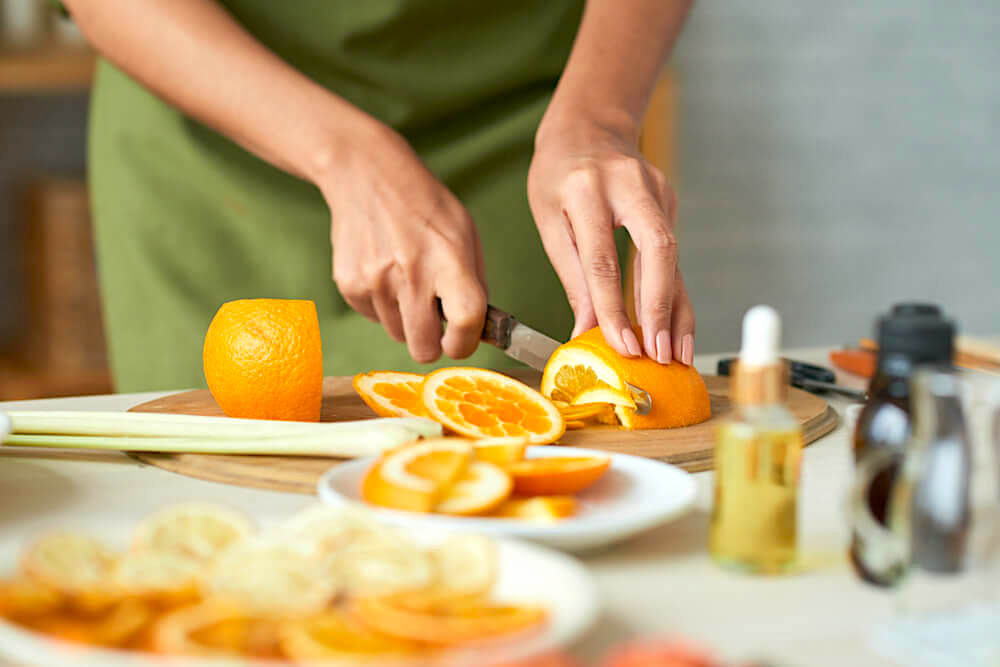Unknown woman slicing up an orange for skincare purposes