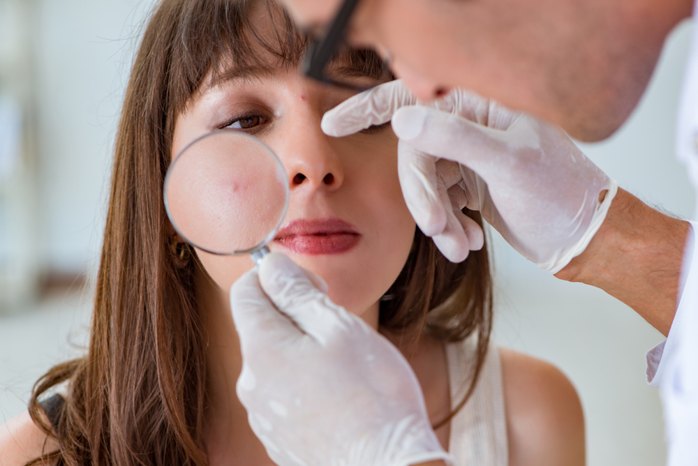 Dermatologist examining pimple of young woman's face