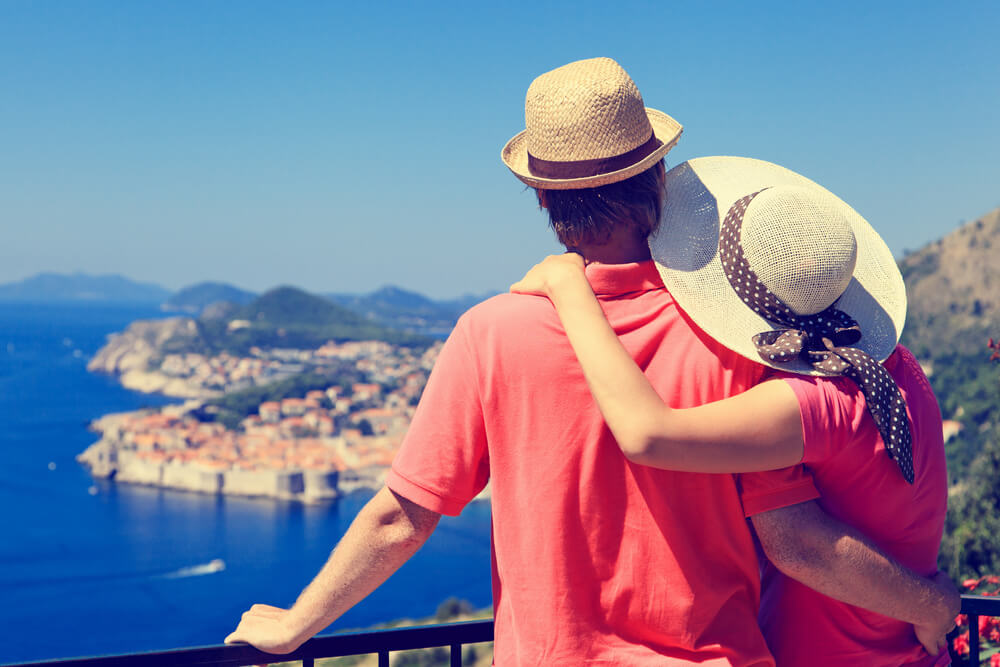 Couple wearing sunhat out on vacation together, looking out over the Mediterranean Sea