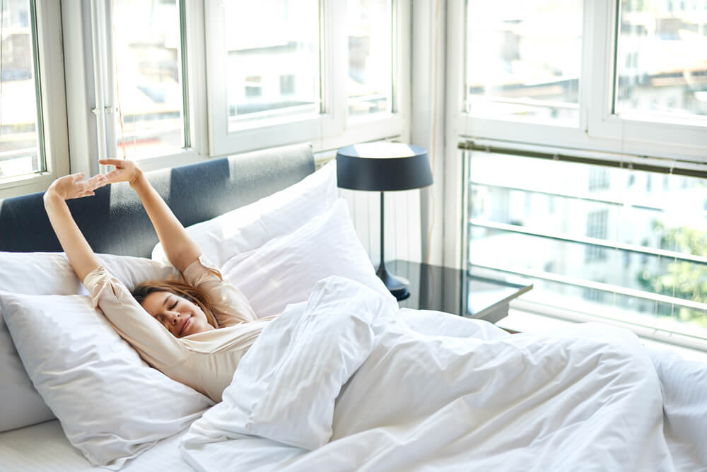 Woman waking up in clean spacious white room