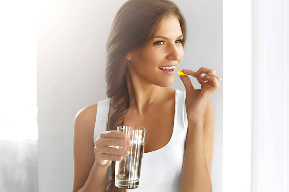 Woman taking in vitamin A pill with a glass of water