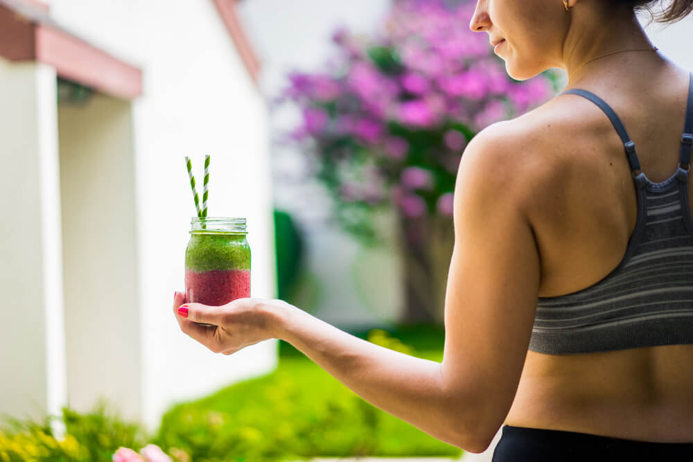 Healthy and fit woman holding a colourful smoothie outdoors